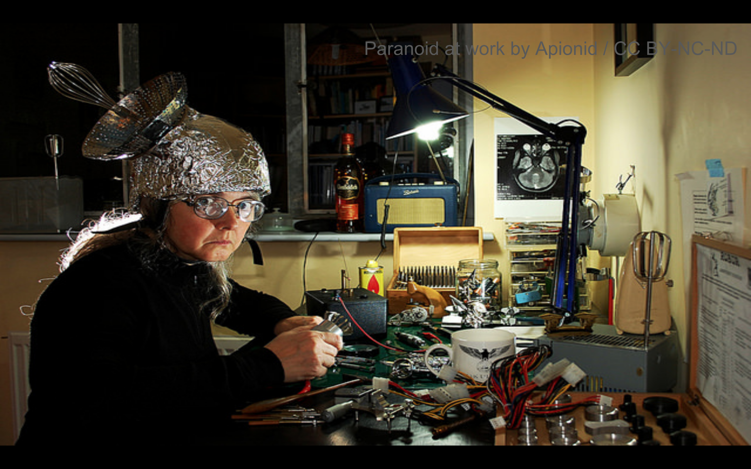 Person wearing a tin foil hat while wiring equipment